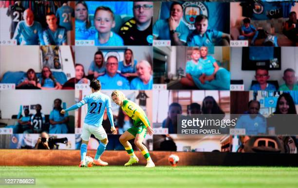 Manchester City's Spanish midfielder David Silva and Norwich City's English midfielder Todd Cantwell play in front of a screen showing supporters...