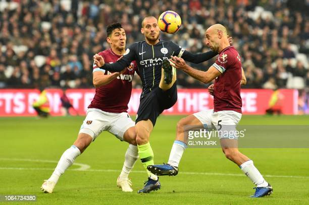 Manchester City's Spanish midfielder David Silva attempts to control the ball under pressure from West Ham United's Argentinian defender Pablo...