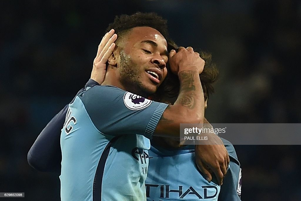 Manchester City's Spanish midfielder David Silva (R) celebrates scoring their second goal with Manchester City's English midfielder Raheem Sterling (L) during the English Premier League football match between Manchester City and Watford at the Etihad Stadium in Manchester, north west England, on December 14, 2016. / AFP / Paul ELLIS / RESTRICTED TO EDITORIAL USE. No use with unauthorized audio, video, data, fixture lists, club/league logos or 'live' services. Online in-match use limited to 75 images, no video emulation. No use in betting, games or single club/league/player publications. /
