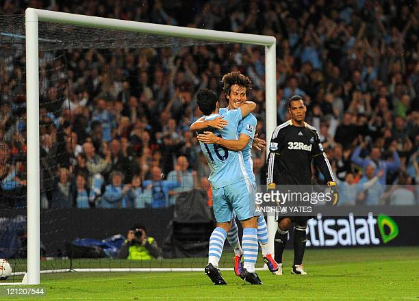 Manchester City's Spanish midfielder David Silva celebrates with Manchester City's Argentinian forward Sergio Aguero after scoring during the English...