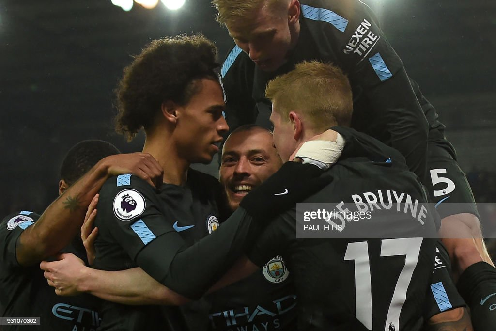 Manchester City's Spanish midfielder David Silva (C) celebrates with teammates after scoring his second goal of the English Premier League football match between Stoke City and Manchester City at the Bet365 Stadium in Stoke-on-Trent, central England on March 12, 2018. / AFP PHOTO / PAUL ELLIS / RESTRICTED TO EDITORIAL USE. No use with unauthorized audio, video, data, fixture lists, club/league logos or 'live' services. Online in-match use limited to 75 images, no video emulation. No use in betting, games or single club/league/player publications. /