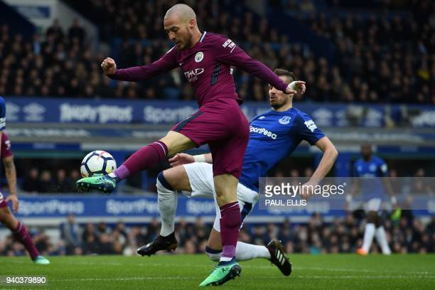 Manchester City's Spanish midfielder David Silva crosses the ball during the English Premier League football match between Everton and Manchester...