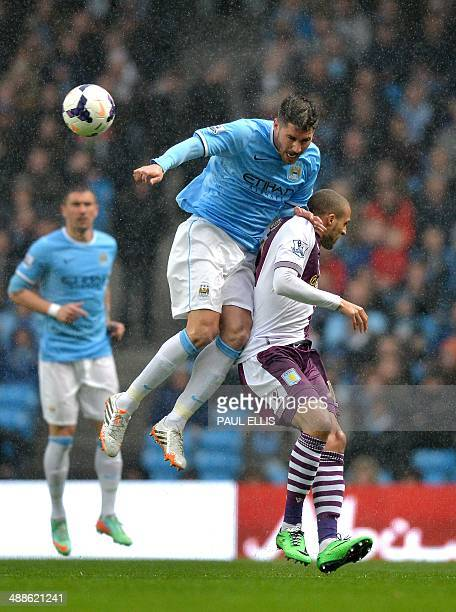Manchester City's Spanish midfielder David Silva jumps for the ball as he vies with Aston Villa's Spanish defender Antonio Luna during the English...