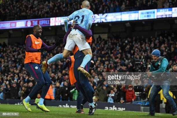 Manchester City's Spanish midfielder David Silva leaps into the arms of Manchester City's Belgian captain Vincent Kompany as he celebrates scoring...