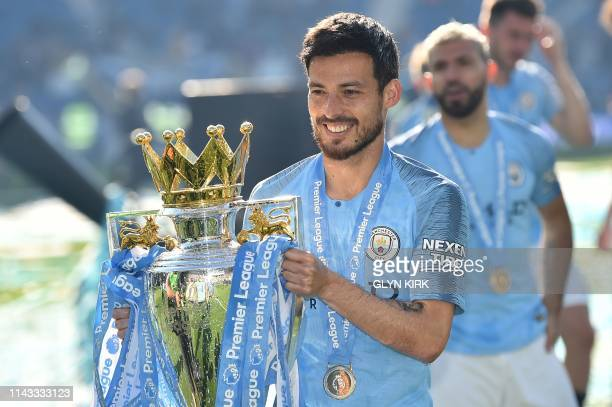 Manchester City's Spanish midfielder David Silva poses with the Premier League trophy after their 41 victory in the English Premier League football...
