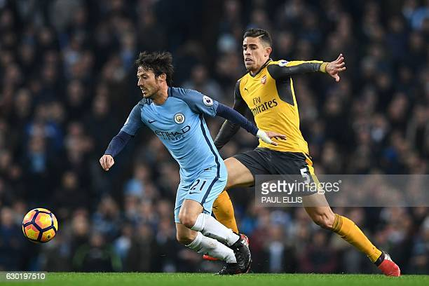 Manchester City's Spanish midfielder David Silva vies with Arsenal's Brazilian defender Gabriel during the English Premier League football match...