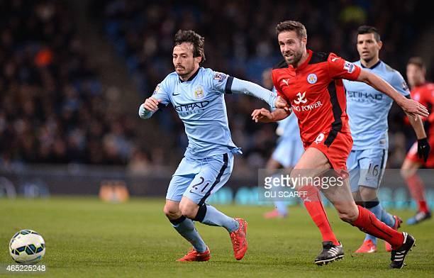 Manchester City's Spanish midfielder David Silva vies with Leicester City's English defender Matthew Upson during the English Premier League football...