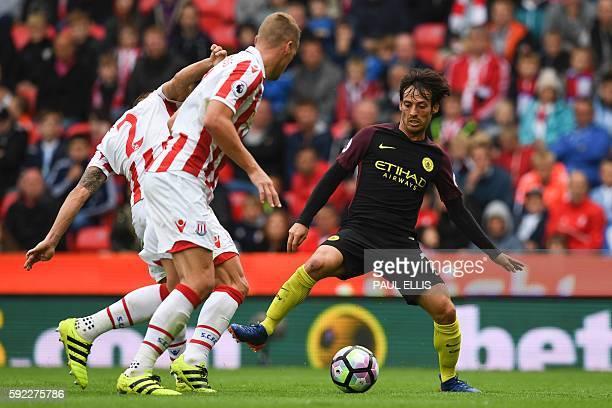 Manchester City's Spanish midfielder David Silva vies with Stoke City's Englishborn Scottish defender Phil Bardsley and Stoke City's English defender...