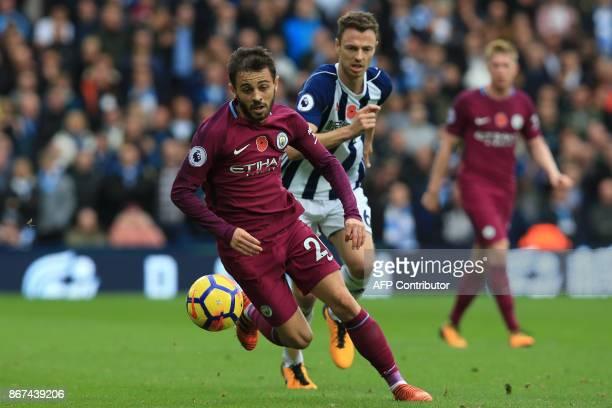 Manchester City's Spanish midfielder David Silva vies with West Bromwich Albion's Northern Irish defender Jonny Evans during the English Premier...