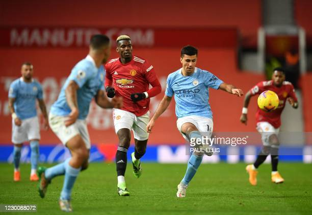 Manchester City's Spanish midfielder Rodri passes the ball during the English Premier League football match between Manchester United and Manchester...