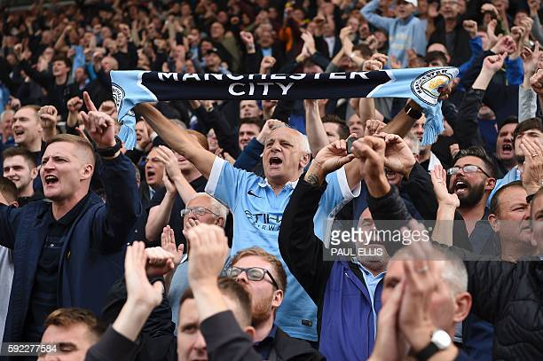 Manchester City's supporters celebrate in the stands after the English Premier League football match between Stoke City and Manchester City at the...