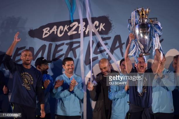 Manchester City's Ukrainian midfielder Oleksandr Zinchenko shows the Premier League trophy to supporters outside the Etihad Stadium in Manchester...