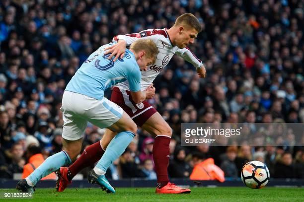 Manchester City's Ukrainian midfielder Oleksandr Zinchenko tangles with Burnley's Icelandic midfielder Johann Berg Gudmundsson during the English FA...