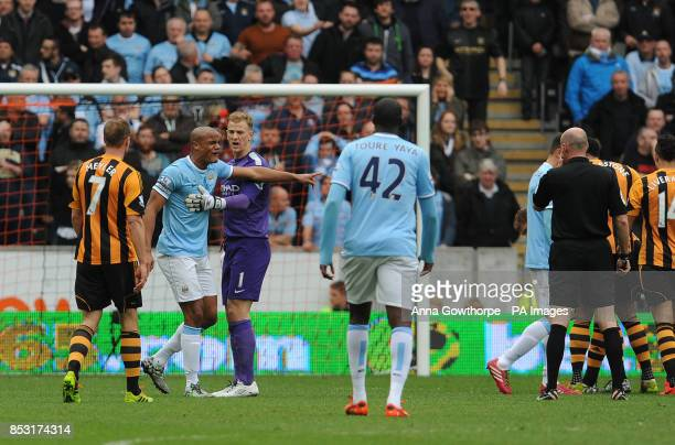 Manchester City's Vincent Kompany is held back by Joe Hart as he argues with referee Lee Mason after being sent off during the Barclays Premier...