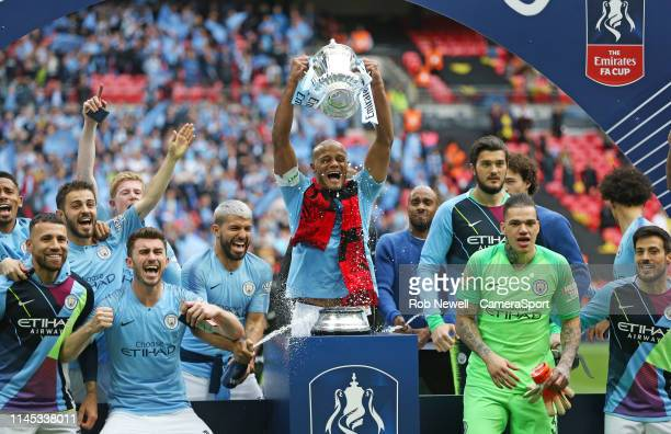 Manchester City's Vincent Kompany lifts the trophy during the FA Cup Final match between Manchester City and Watford at Wembley Stadium on May 18,...