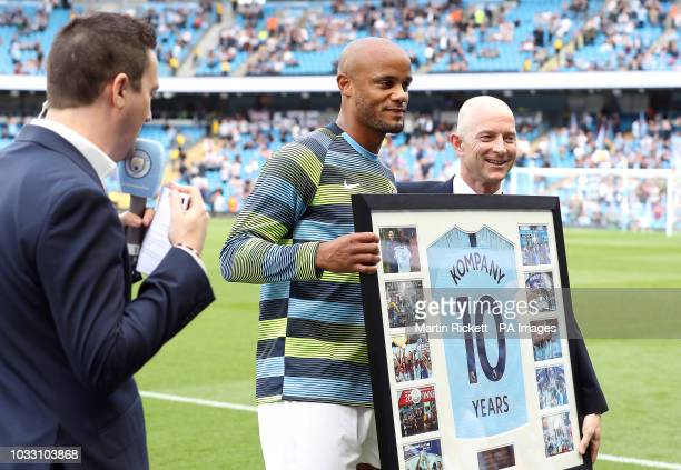 Manchester City's Vincent Kompany receives a framed shirt after celebraring 10 years with the club before the match