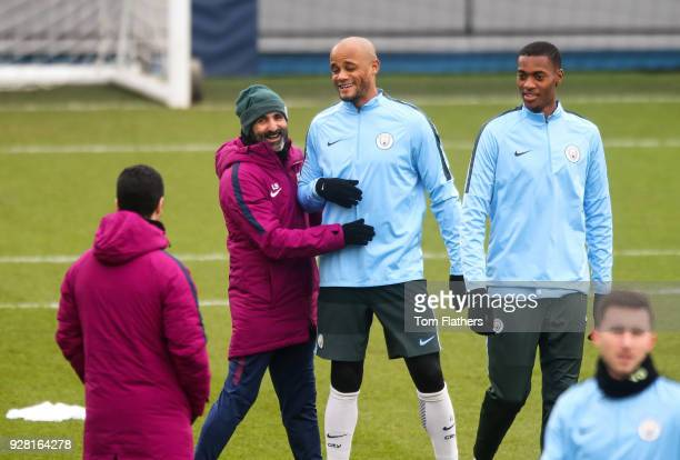 Manchester City's Vincent Kompany shares a joke with coach Lorenzo Buenaventura during the open training session at Manchester City Football Academy...