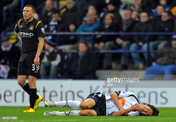 Manchester City's Welsh forward Craig Bellamy looks on as Bolton Wanderers' South Korean midfielder Lee Chung-Yong lies injured during the English...