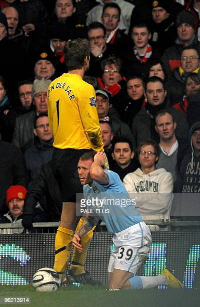 Manchester City's Welsh forward Craig Bellamy reacts after being hit on the head by an object thrown from the crowd during the English Carling Cup...