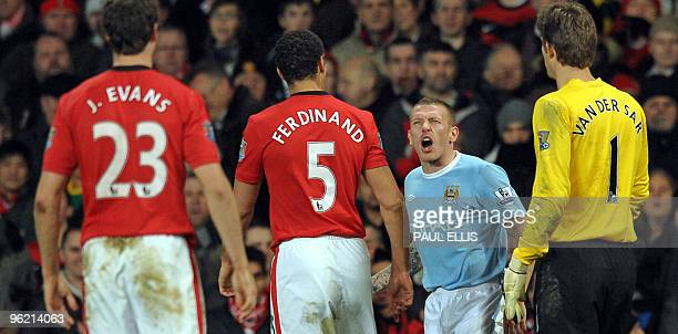 Manchester City's Welsh forward Craig Bellamy reacts towards Manchester United's English defender Rio Ferdinand after being hit on the head by an...