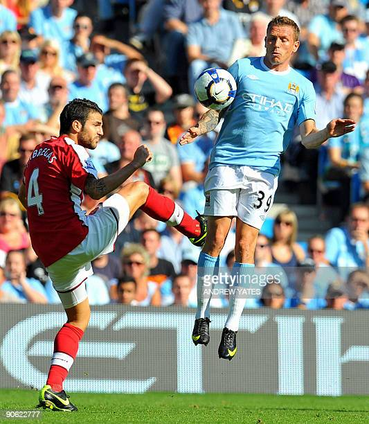 Manchester City's Welsh forward Craig Bellamy vies with Arsenal's Spanish midfielder Cesc Fabregas during the English Premier League football match...
