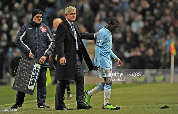 Manchester City's Welsh manager Mark Hughes consoles English midfielder Shaun WrightPhillips as he is substituted during the English Premier League...