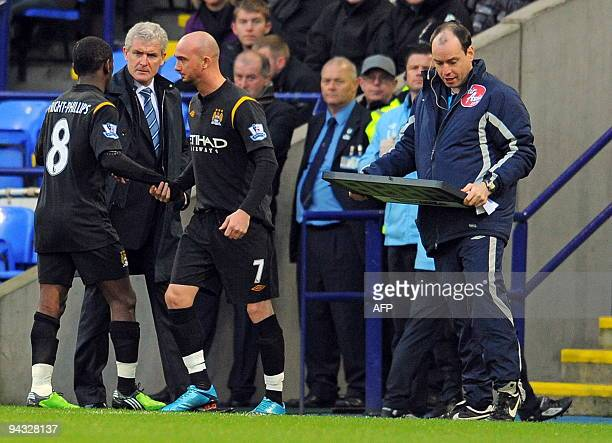 Manchester City's Welsh manager Mark Hughes speaks to English midfielder Shaun WrightPhillips after he was substituted during the English Premier...