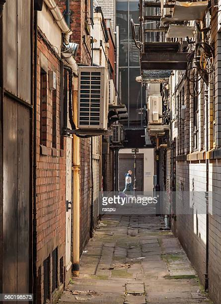 manchester, small alley - black alley stock photos and pictures