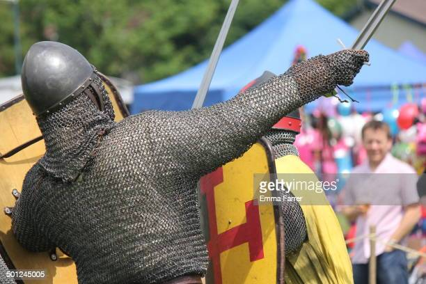 Man from Historia Normannis 12th century battle reenactment group in chain mail armour taking part in a battle at Prestwich Carnival in North...