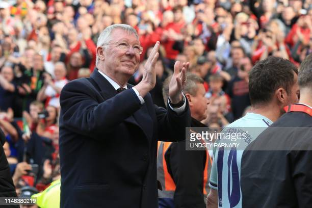 Manchester United '99 Legends manager Alex Ferguson gestures to supporters as he leaves after the Treble Reunion 20th anniversary football match...