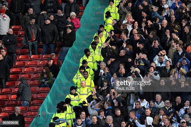 Manchester United and Leeds United supporters are kept apart during their English FA Cup football match at Old Trafford in Manchester northwest...
