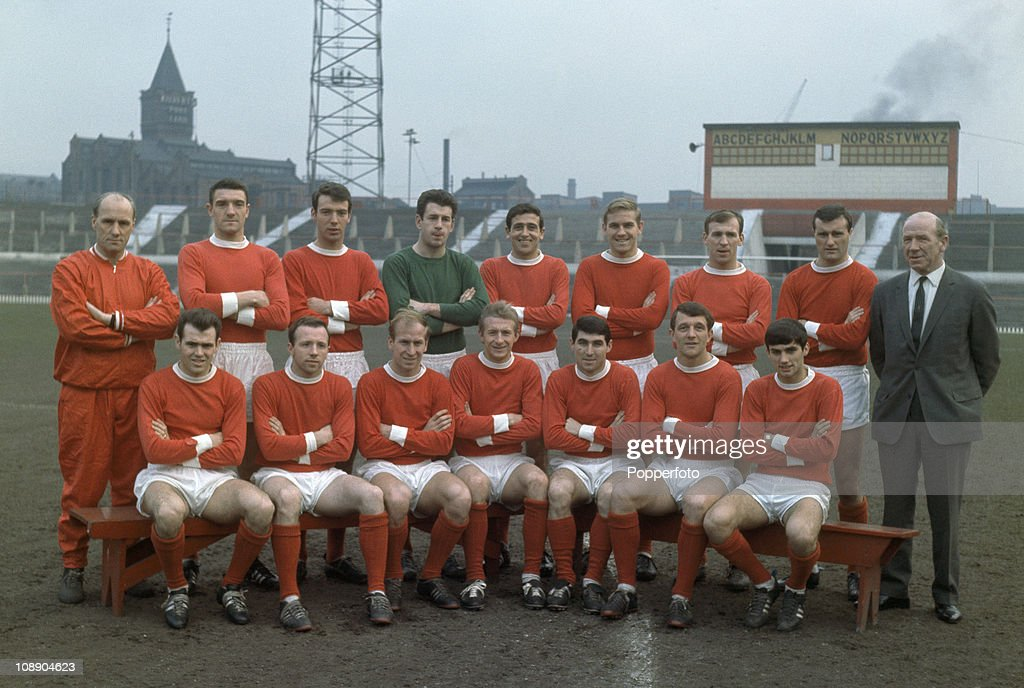 Manchester United at Old Trafford, Manchester on 17th February 1965. Manchester United were League Division One champions for the season 1964-1965. Back row, left to right: Jack Crompton (trainer), Bill Foulkes, David Sadler, Pat Dunne, Shay Brennan, Graham Moore, Pat Crerand, Noel Cantwell and Matt Busby (manager); front row, left to right: John Connelly, Nobby Stiles, Bobby Charlton, Denis Law, Tony Dunne, David Herd and George Best.