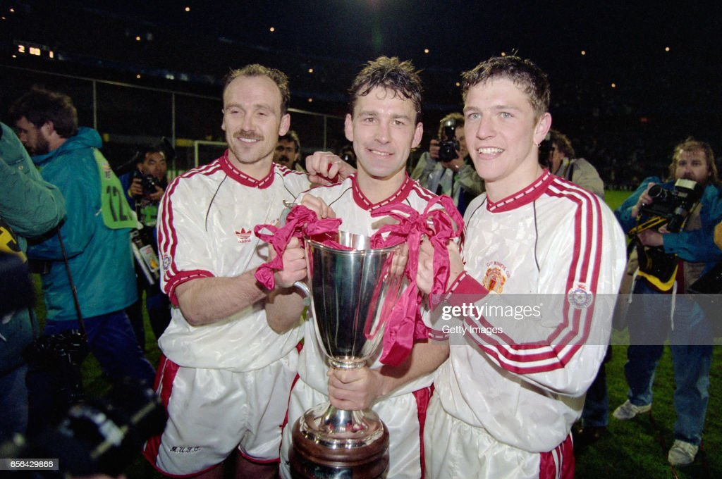 Manchester United captain Bryan Robson (c) celebrates with the trophy with team mates Mike Phelan (l) and Lee Sharpe (r) after the 1991 UEFA European Cup Winners Cup Final between Manchester United and Barcelona on May 15th, 1991 in Rotterdam, Holland.