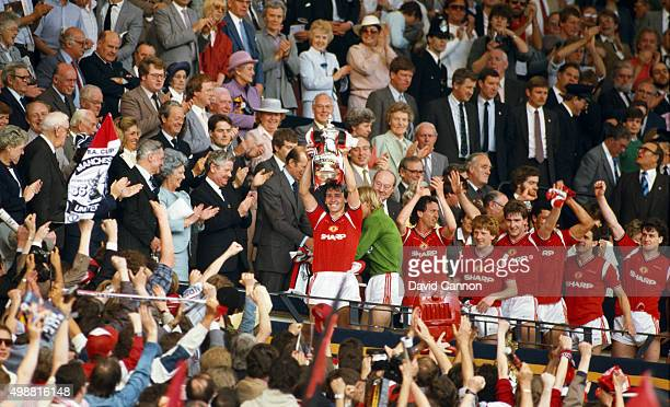 Manchester United captain Bryan Robson holds aloft the trophy after the 1985 FA Cup Final between Manchester United and Everton at Wembley Stadium on...