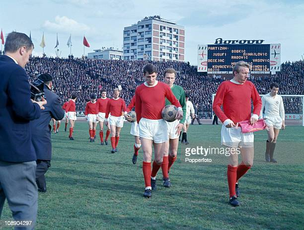 Manchester United captain Denis Law leads the team onto the field followed by David Herd and goalkeeper Harry Gregg prior to the start of the...