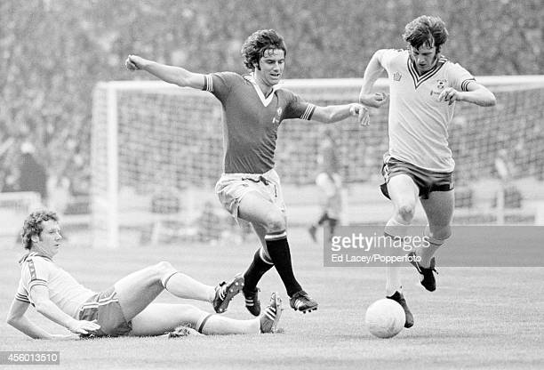 Manchester United captain Martin Buchan is out-numbered by Jim Steele and Mick Channon of Southampton during the FA Cup Final at Wembley Stadium on...