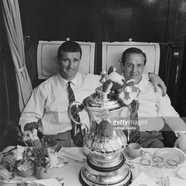 Manchester United captain Noel Cantwell pictured on left with wing half Maurice Setters and the FA Cup trophy on the train back home the day after...