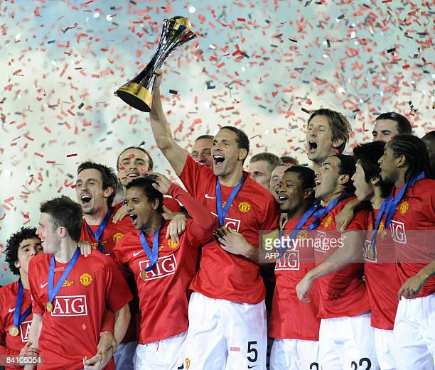 Manchester United captain Rio Ferdinand raises the trophy to celebrate with his teammates after winning the FIFA Club World Cup against Ecuador's...