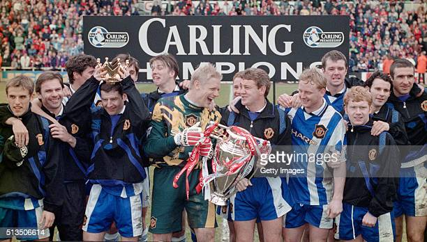 Manchester United captain Steve Bruce and goalkeeper Peter Schmeichel celebrate with team mates and the premiership trophy after winning the 1995/96...