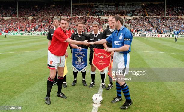 Manchester United captain Steve Bruce exchanges pennants at the coin toss with his opposite number Dave Watson as referee Gerald Ashby looks on with...