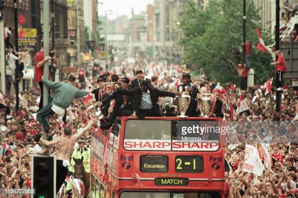 Manchester United celebrate winning the treble as the jubilant team make their way through Manchester during an open top bus parade. Teddy Sheringham...