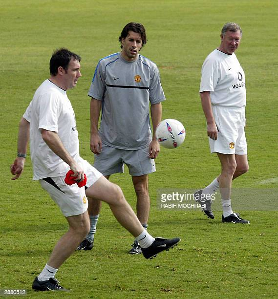 Manchester United coach Sir Alex Ferguson watch Ruud Van Nistelrooy and goalkeeper trainer Tony Coton during training session in Dubai 19 January...