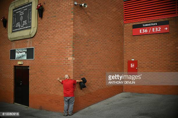 Manchester United fan embraces the side of Old Trafford stadium ahead of the English Premier League football match between Manchester United and...