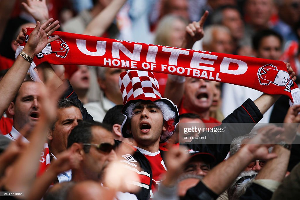 A Manchester United fan holding his scarf and singing during the FA Cup Final between Chelsea and Manchester Utd at Wembley Stadium on May 19th, 2007 in Wembley, London, U.K.