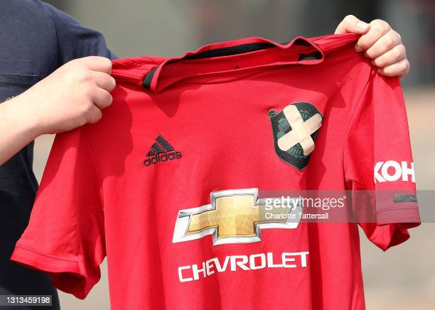 Manchester United fan holds up a football shirt with two plasters covering the club badge outside Old Trafford on April 20, 2021 in Manchester,...