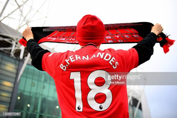 Manchester United fan holds up a scarf outside the stadium while wearing a shirt with new signing Bruno Fernandes name and number outside the stadium...