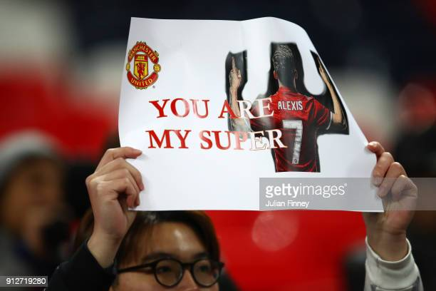 Manchester United fan holds up an Alexis Sanchez poster prior to the Premier League match between Tottenham Hotspur and Manchester United at Wembley...