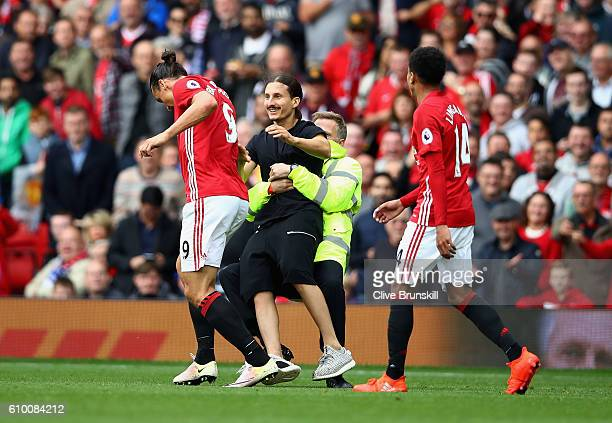 Manchester United fan invades the pitch and attempts to reach Zlatan Ibrahimovic of Manchester United but is stopped by stewards during the Premier...