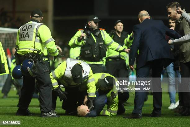 Manchester United fan is restrained at the end of the Carabao Cup QuarterFinal match between Bristol City and Manchester United at Ashton Gate on...
