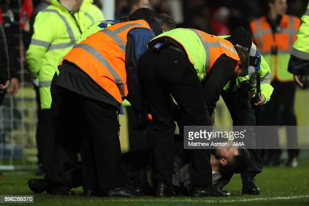 Manchester United fan is restrained during the Carabao Cup QuarterFinal match between Bristol City and Manchester United at Ashton Gate on December...